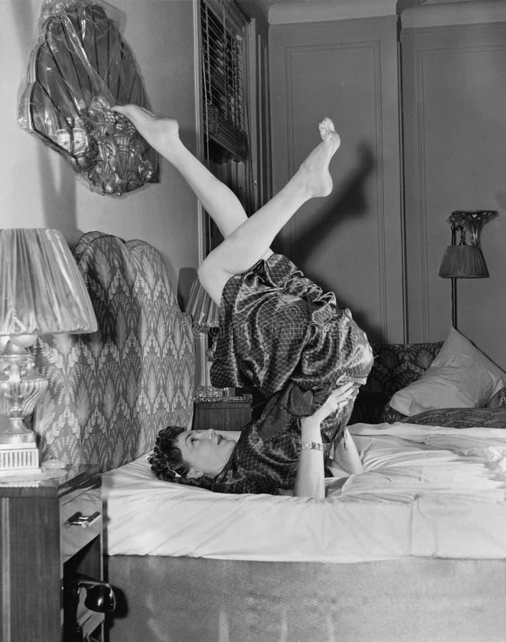 Γυναίκα που κάνει τη γιόγκα στο κρεβάτι (όλα τα πρόσωπα που απεικονίζονται δεν ζουν περισσότερο και κανένα κτήμα δεν υπάρχει Εξου στοκ φωτογραφία