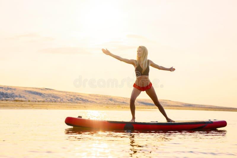 Γυναίκα που κάνει τις ασκήσεις γιόγκας στον πίνακα κουπιών στο νερό στοκ φωτογραφία