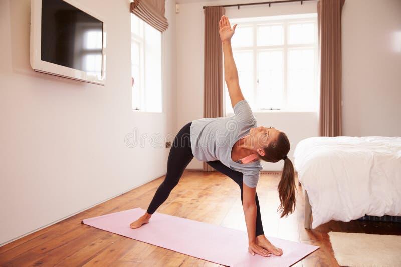 Γυναίκα που κάνει τις ασκήσεις ικανότητας γιόγκας στο χαλί στην κρεβατοκάμαρα στοκ εικόνες