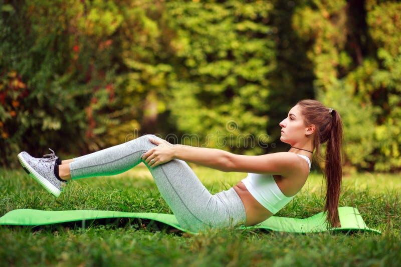 Γυναίκα που κάνει τις ασκήσεις ικανότητας στο θερινό πάρκο, workout υπαίθρια στοκ φωτογραφίες