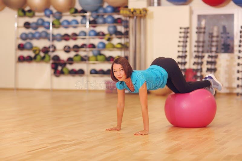 Γυναίκα που κάνει τις ασκήσεις με την κόκκινη κατάλληλη σφαίρα στην κατηγορία γυμναστικής ικανότητας Η σφαίρα ικανότητας βοηθά τι στοκ εικόνες