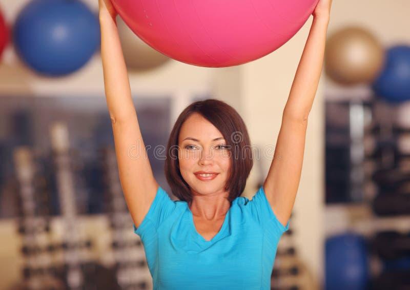 Γυναίκα που κάνει τις ασκήσεις με τη ρόδινη κατάλληλη σφαίρα στην κατηγορία γυμναστικής ικανότητας Η σφαίρα ικανότητας βοηθά τις  στοκ εικόνα