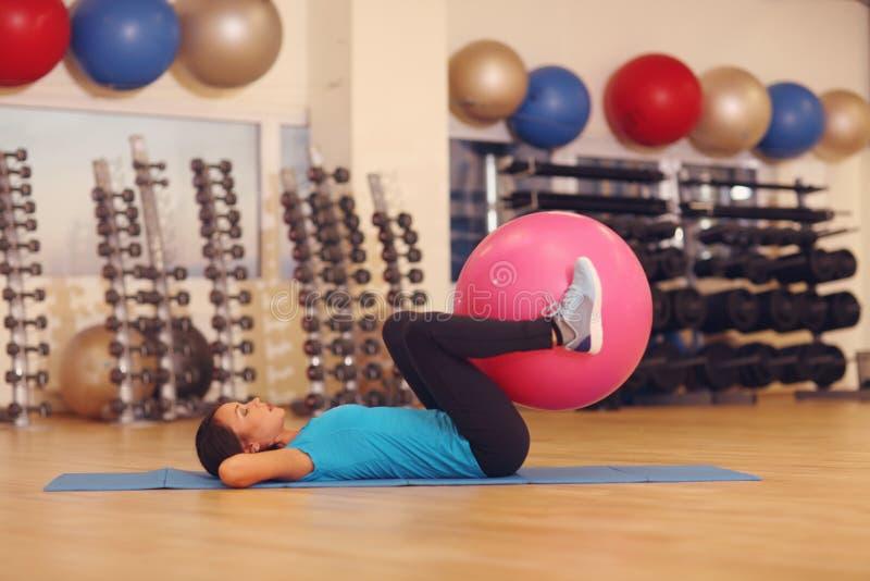 Γυναίκα που κάνει τις ασκήσεις με τη ρόδινη κατάλληλη σφαίρα στην κατηγορία γυμναστικής ικανότητας Η σφαίρα ικανότητας βοηθά τις  στοκ εικόνα με δικαίωμα ελεύθερης χρήσης