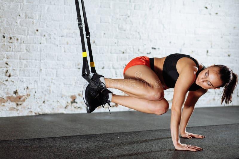 Γυναίκα που κάνει το ώθηση-UPS ενώ πόδια που κρεμούν στο trx στοκ εικόνες