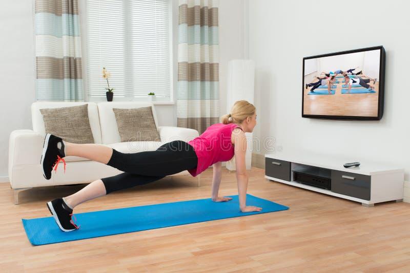 Γυναίκα που κάνει Workout στο εσωτερικό στοκ εικόνα