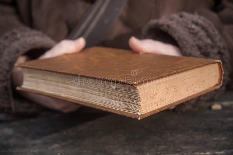 Γυναίκα που καλαμώνει ένα παλαιό βιβλίο σε υπαίθριο στοκ φωτογραφίες
