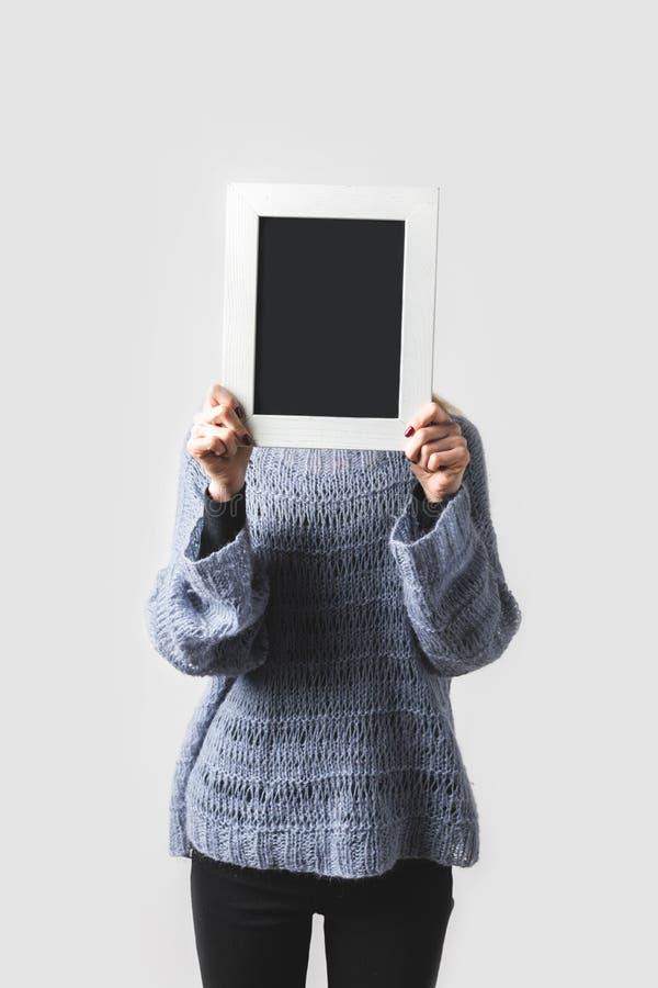 γυναίκα που καλύπτει το πρόσωπο με τον κενό μαύρο πίνακα στοκ εικόνες