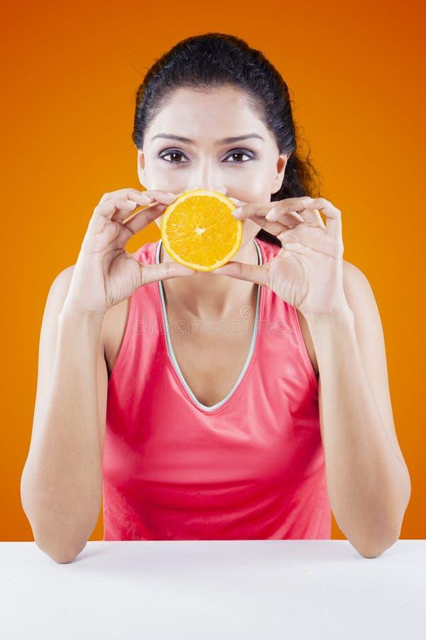 Γυναίκα που καλύπτει το στόμα της με τα πορτοκαλιά φρούτα στοκ φωτογραφία με δικαίωμα ελεύθερης χρήσης