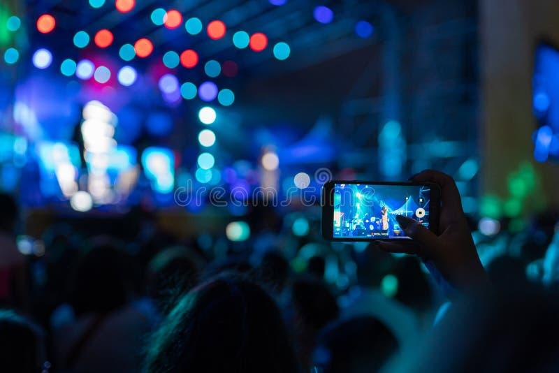 Γυναίκα που καταγράφει μια συναυλία στο κινητό τηλέφωνό της στοκ φωτογραφία με δικαίωμα ελεύθερης χρήσης