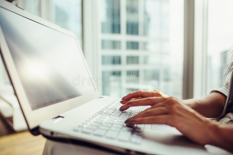 Γυναίκα που καταναλώνει τη συνεδρίαση lap-top στο σύγχρονο γραφείο κοντά στοκ φωτογραφία