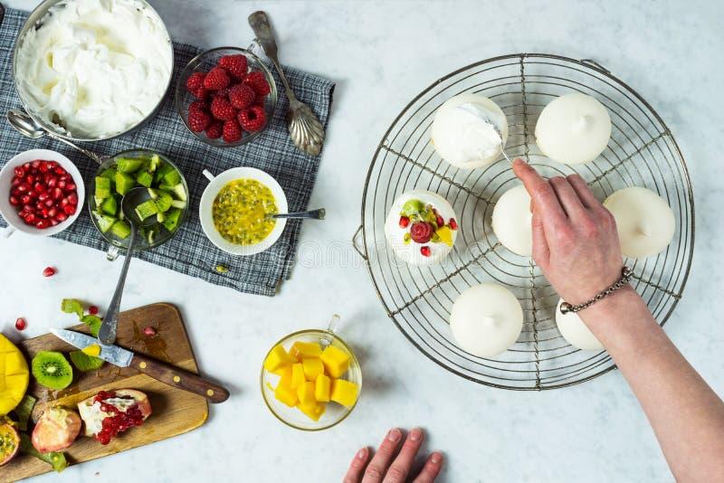 Γυναίκα που κατασκευάζει τα μίνι τροπικά φρούτα Pavlovas στοκ εικόνα με δικαίωμα ελεύθερης χρήσης