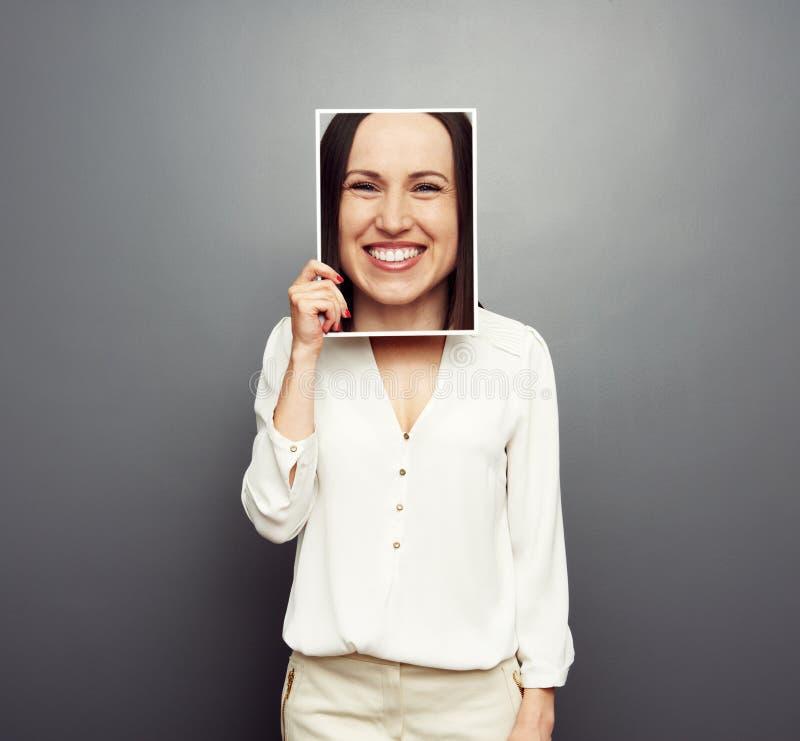 Γυναίκα που καλύπτει την εικόνα με το μεγάλο ευτυχές πρόσωπο στοκ φωτογραφία