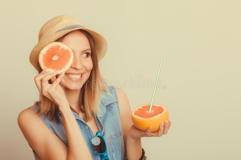 Γυναίκα που καλύπτει το μάτι της με το γκρέιπφρουτ Καλοκαίρι διασκέδασης στοκ εικόνες