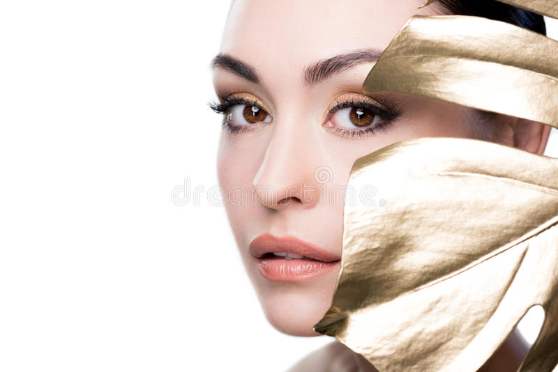 Γυναίκα που καλύπτει το πρόσωπο με το μεγάλο χρυσό φύλλο που απομονώνεται στο λευκό στοκ εικόνα