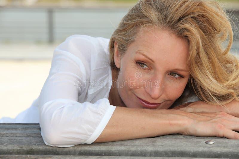 Γυναίκα που κλίνει σε έναν πάγκο στοκ εικόνες με δικαίωμα ελεύθερης χρήσης