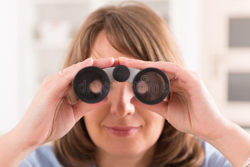 Γυναίκα που κοιτάζει μέσω διοφθαλμικού στοκ εικόνα