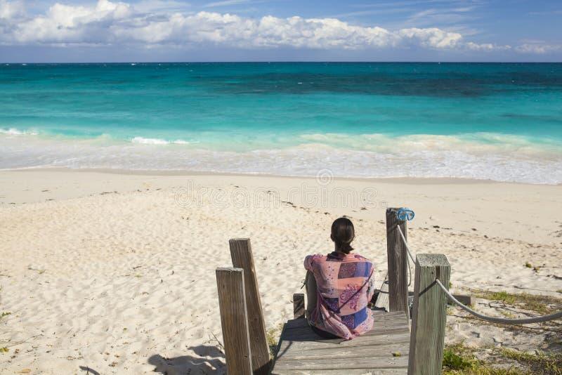 Γυναίκα που κοιτάζει πέρα από την τροπική παραλία στοκ εικόνα
