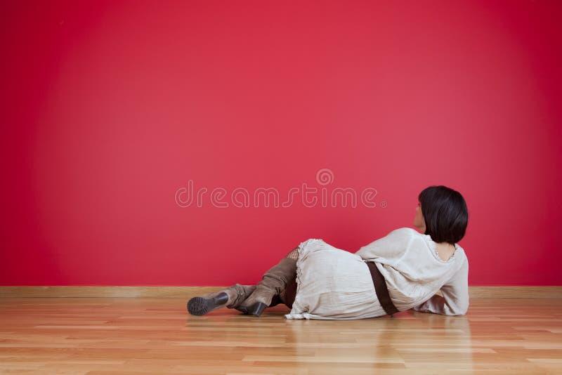 Γυναίκα που κοιτάζει σε έναν κόκκινο τοίχο στοκ εικόνες
