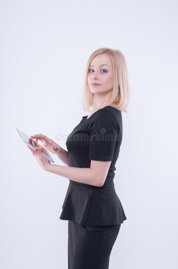 Γυναίκα που κοιτάζει στην άσπρη ταμπλέτα στα χέρια της Κλείστε επάνω του νέου ξανθού όμορφου κοριτσιού στο μαύρο φόρεμα χρησιμοπο στοκ εικόνες