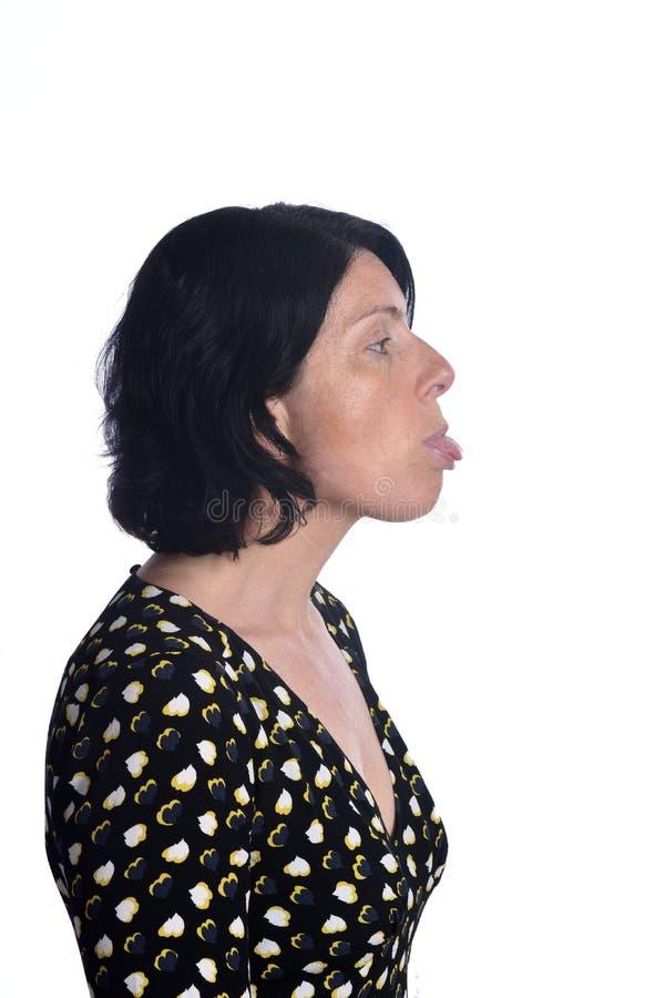 Γυναίκα που κολλά έξω τη γλώσσα της στο άσπρο υπόβαθρο στοκ εικόνα