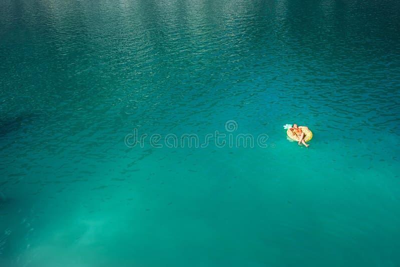 Γυναίκα που κολυμπά στο διογκώσιμο δαχτυλίδι ανανά κατά τη τοπ εναέρια άποψη λιμνών βουνών Ξένοιαστη εικόνα έννοιας διάρκειας ζωή στοκ φωτογραφία