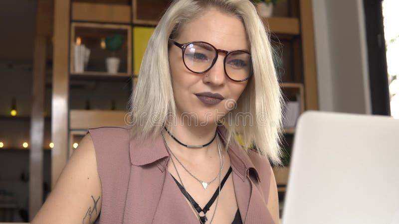 Γυναίκα που κουβεντιάζει στο lap-top και το χαμόγελο στοκ φωτογραφίες