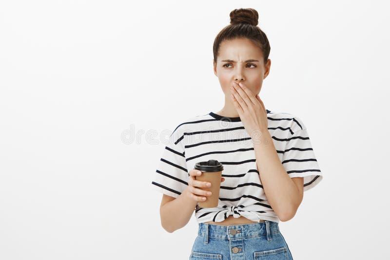 Γυναίκα που κουράζεται επιτυχής Δημιουργική νέα γυναίκα σπουδαστής με το κουλούρι hairstyle, συνοφρύωμα και χασμουμένος, κράτημα στοκ εικόνα