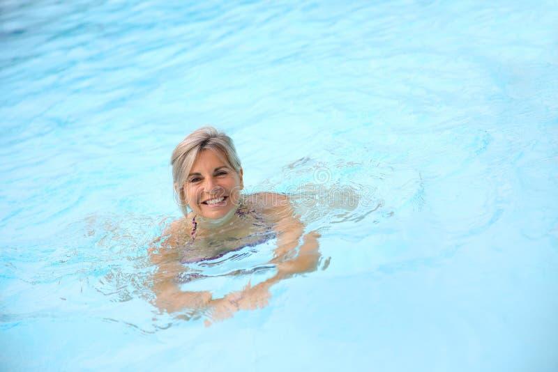 Γυναίκα που κολυμπά στην μπλε λίμνη στοκ εικόνα