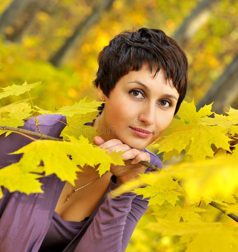 Γυναίκα που κρατά έναν κλάδο με τα κίτρινα φύλλα σφενδάμου στοκ εικόνες