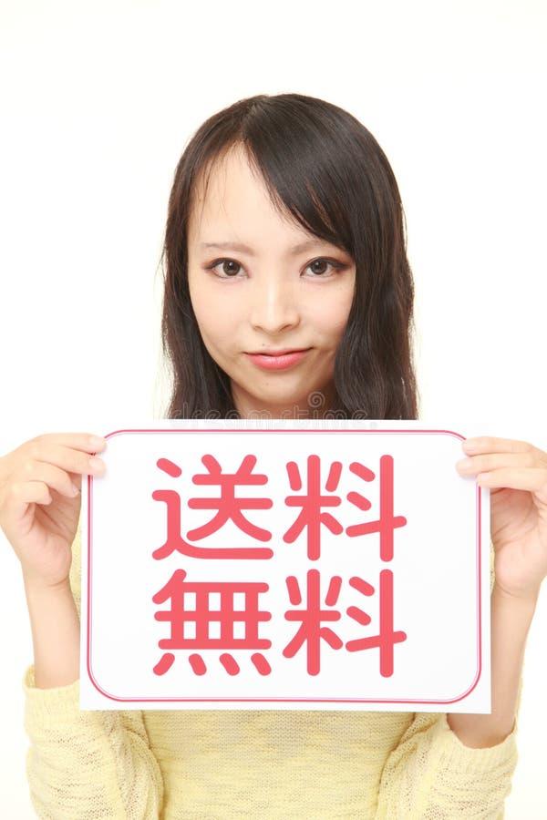 Γυναίκα που κρατά έναν πίνακα μηνυμάτων με την ΕΛΕΥΘΕΡΗ ΝΑΥΤΙΛΙΑ φράσης KANJI στοκ φωτογραφία με δικαίωμα ελεύθερης χρήσης