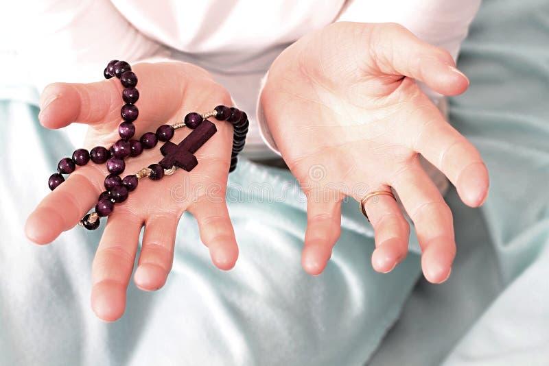 Γυναίκα που κρατά έναν σταυρό με rosary τις χάντρες στοκ εικόνες