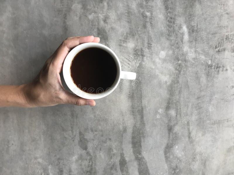 Γυναίκα που κρατά ένα φλυτζάνι του καυτού μαύρου καφέ με το αριστερό χέρι της στον πίνακα τσιμέντου στοκ φωτογραφία με δικαίωμα ελεύθερης χρήσης