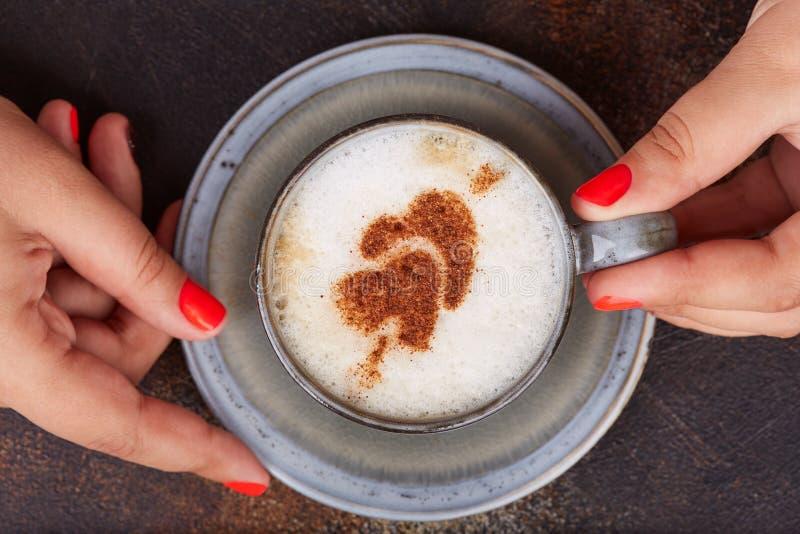 Γυναίκα που κρατά ένα φλυτζάνι του καφέ cappuccino με τις καρδιές κανέλας στην κορυφή στοκ φωτογραφίες