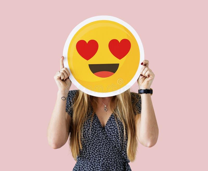 Γυναίκα που κρατά ένα emoji προσώπου στοκ εικόνες