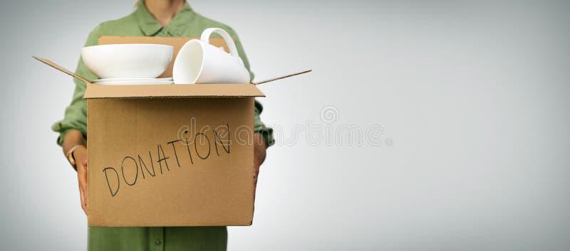 Γυναίκα που κρατά κουτί με οικιακά αντικείμενα για δωρεές σε γκρι φόντο στοκ εικόνες