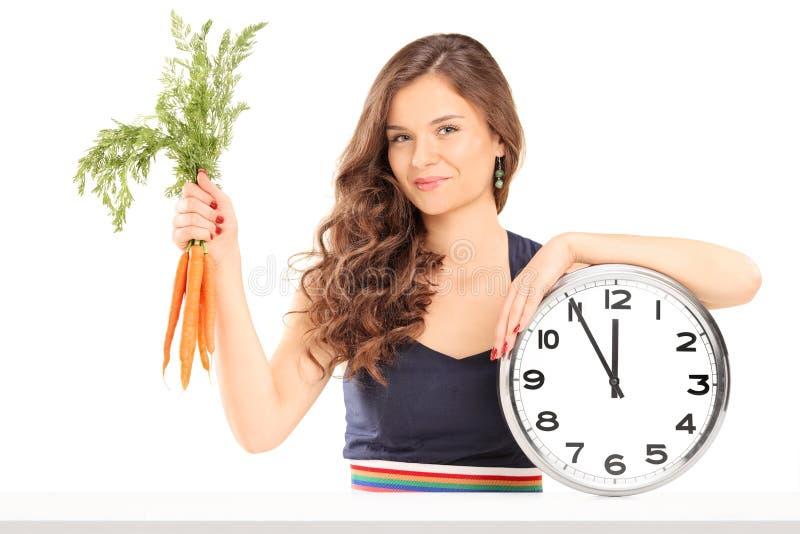 Γυναίκα που κρατά μια δέσμη των καρότων και ενός μεγάλου ρολογιού τοίχων στοκ εικόνα