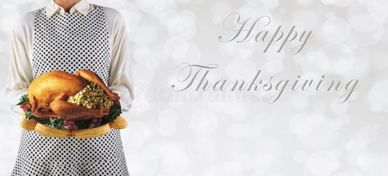 Γυναίκα που κρατά μια ημέρα των ευχαριστιών Τουρκία σε μια πιατέλα άνω του ασημένιου β στοκ εικόνες