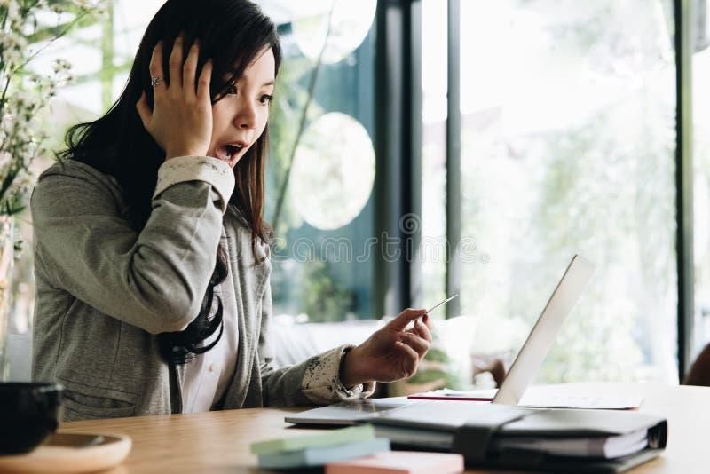 Γυναίκα που κρατά μια πιστωτική κάρτα και που χρησιμοποιεί το φορητό προσωπικό υπολογιστή για on-line στοκ φωτογραφία με δικαίωμα ελεύθερης χρήσης