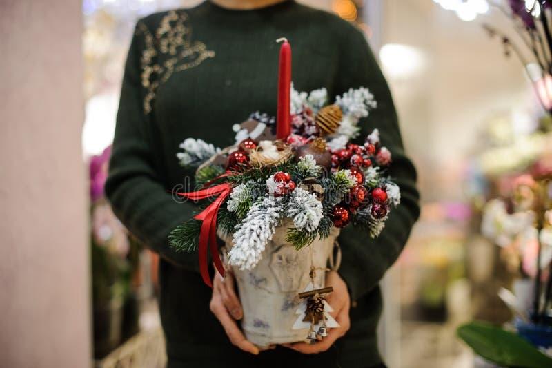 Γυναίκα που κρατά μια σύνθεση Χριστουγέννων φιαγμένη από δέντρο έλατου, σφαίρες γυαλιού, κώνους, χιόνι και κερί στοκ εικόνες