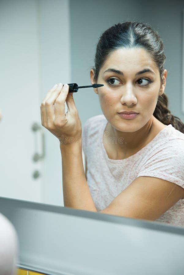 Γυναίκα που κρατά μια mascara βούρτσα στο πρόσωπό της στοκ εικόνα με δικαίωμα ελεύθερης χρήσης