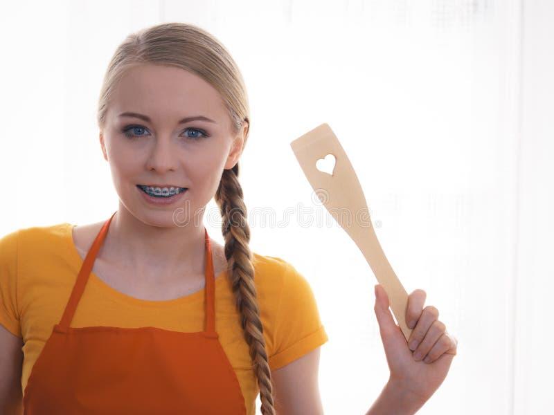 Γυναίκα που κρατά ξύλινο spatula με την καρδιά στοκ εικόνες