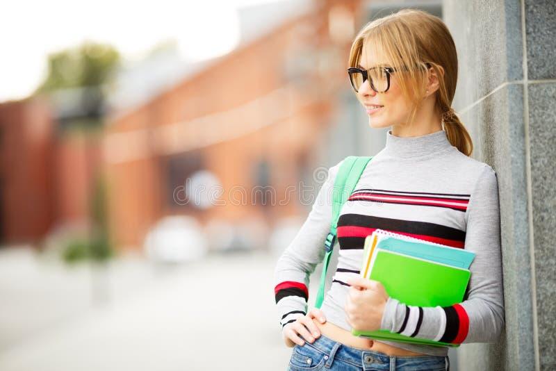 Γυναίκα που κρατά τα βιβλία της στο πάρκο πανεπιστημιουπόλεων στοκ φωτογραφία με δικαίωμα ελεύθερης χρήσης