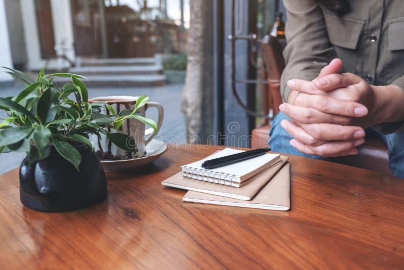 Γυναίκα που κρατά τα χέρια της καθμένος στο σπίτι στοκ εικόνα