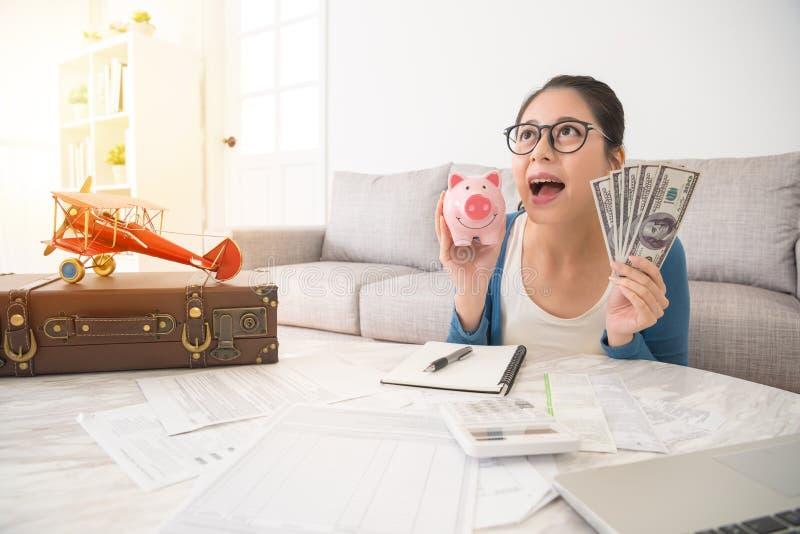 Γυναίκα που κρατά τα piggy χρήματα μετρητών ανατρέχοντας ευτυχώς στοκ εικόνες