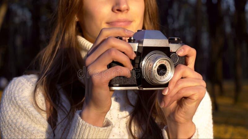 Γυναίκα που κρατά την παλαιά εκλεκτής ποιότητας κάμερα, που ψάχνει τον πυροβολισμό της όμορφης φύσης φθινοπώρου στοκ εικόνες