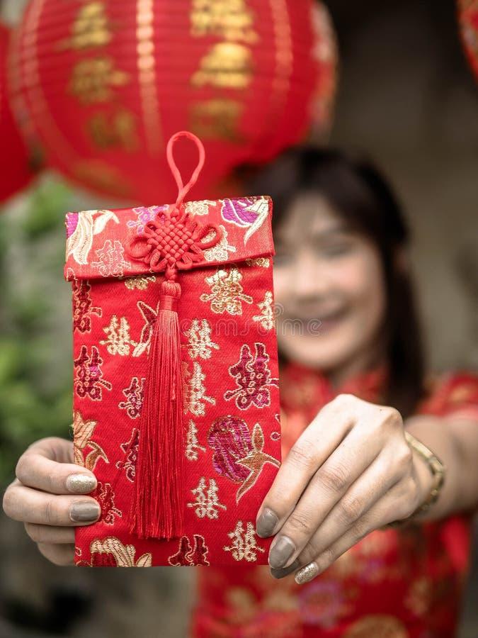 Γυναίκα που κρατά τον κόκκινο φάκελο που δίνει στο κινεζικό νέο φεστιβάλ έτους κινεζικό νέο έτος στοκ εικόνα