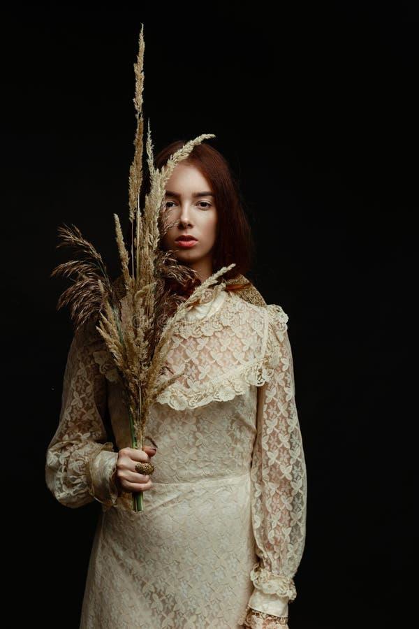 Γυναίκα που κρατά τον ξηρό κάλαμο στοκ εικόνες