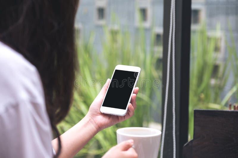 Γυναίκα που κρατά το άσπρο κινητό τηλέφωνο με την κενή μαύρη οθόνη πίνοντας τον καφέ στον καφέ στοκ φωτογραφία
