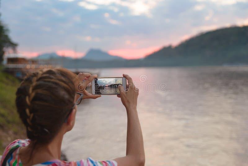 Γυναίκα που κρατά το έξυπνο τηλέφωνο που φωτογραφίζει το ποταμό Μεκόνγκ σε Luang Prabang Λάος, δραματικός ουρανός ηλιοβασιλέματος στοκ φωτογραφία με δικαίωμα ελεύθερης χρήσης