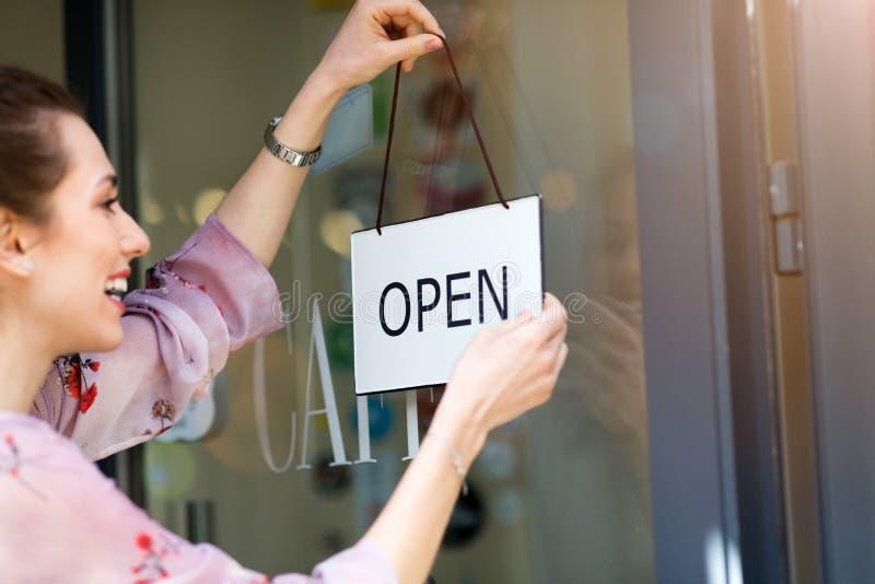 Γυναίκα που κρατά το ανοικτό σημάδι στον καφέ στοκ φωτογραφία με δικαίωμα ελεύθερης χρήσης